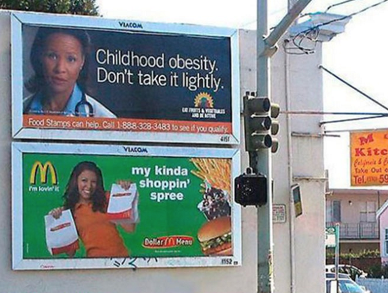 """Funny photo of a billboard that reads, """"Childhood obesity. Don't take it lightly"""" above a billboard advertising McDonald's that reads, """"My kinda shoppin' spree"""""""