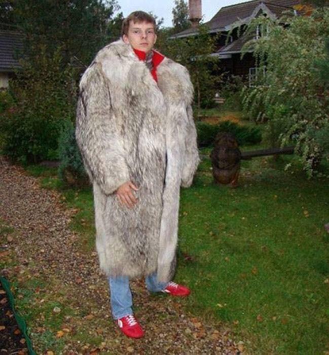 young man wearing a huge fur coat