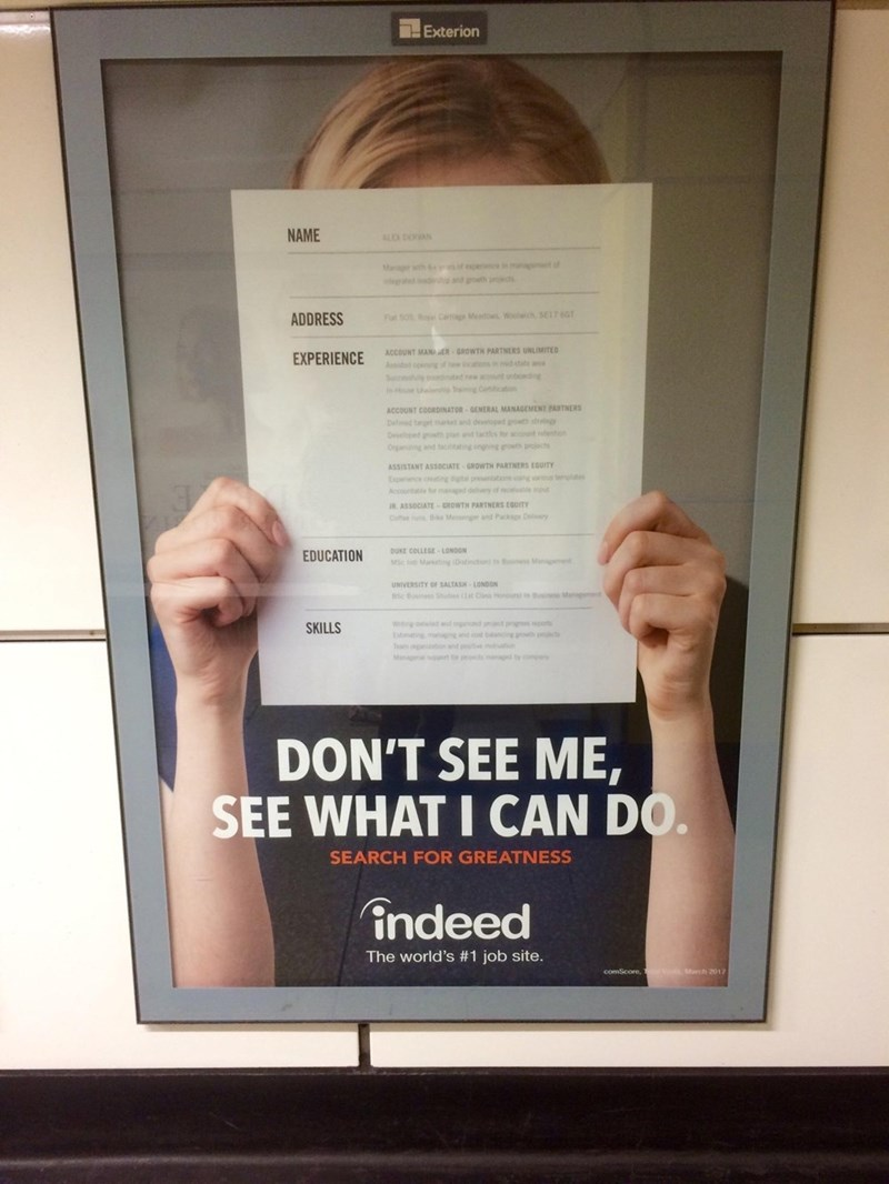 """'Indeed' advertisement that reads, """"Don't see me, see what I can do"""" over a photo of a person holding up their resume over their face"""