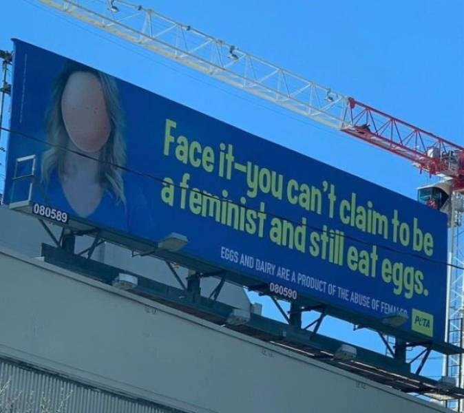 """Photo of a PETA billboard that reads, """"Face it - you can't claim to be a feminist and still eat eggs"""""""