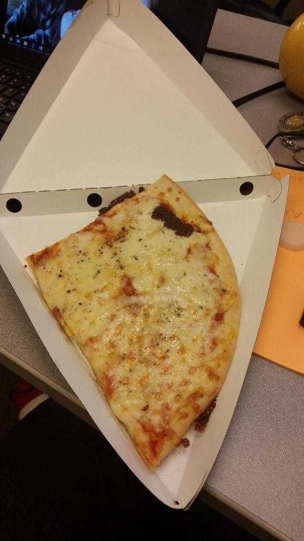 Photo of a piece of pizza that does not properly fit into a triangle-shaped pizza box
