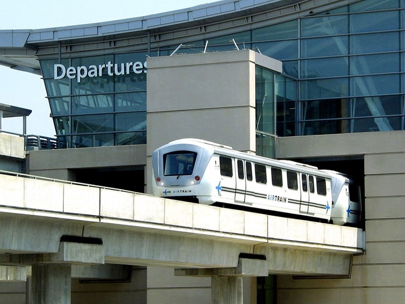 white JFK AirTrain emerging from the departures building in the airport