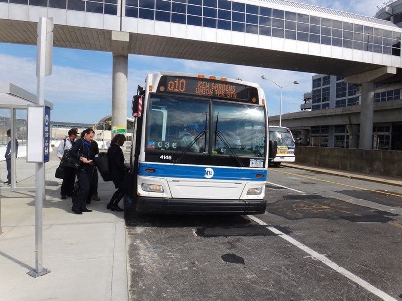 a blue and white Q10 bus pulling up at a bus stop at JFK airport