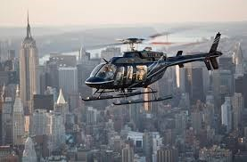 a sleek black helicopter flying over New York at sunset with buildings in the background