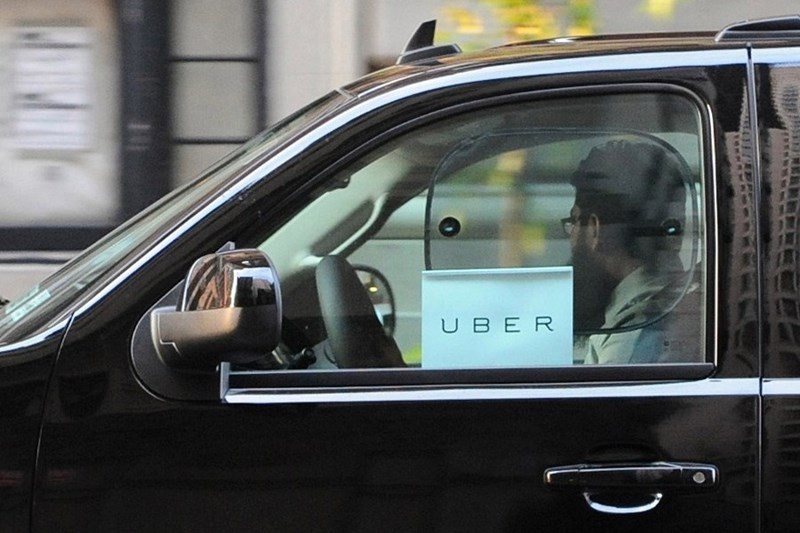 the exterior of a black SUV Uber showing the driver through the window, a man with his head turned away, and a sign saying 'Uber' in the window