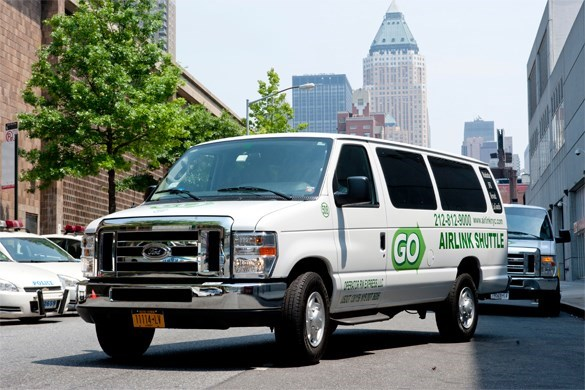 a white Go AirLink NYC van parks in the middle of a street with high rise buildings seen behind it