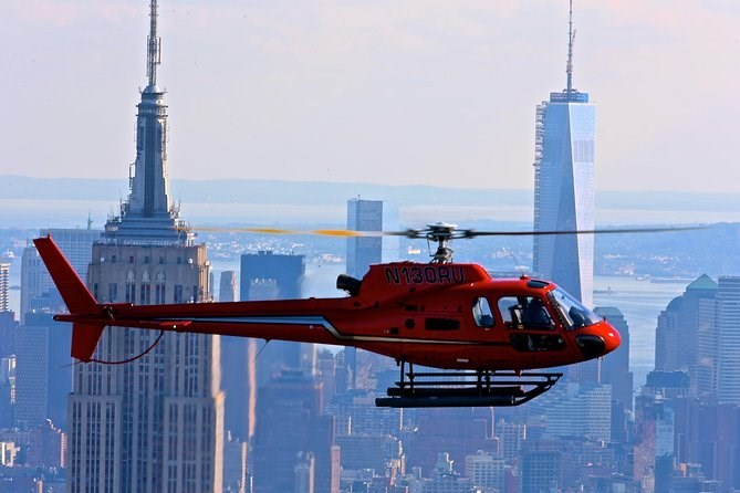 a red helicopter with blurred propellers flying over new york with skyscrapers in the background