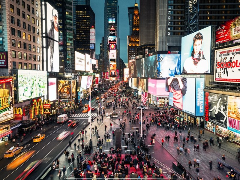 A view of times square from above street level at night, with illuminated billboards and moving cars and people