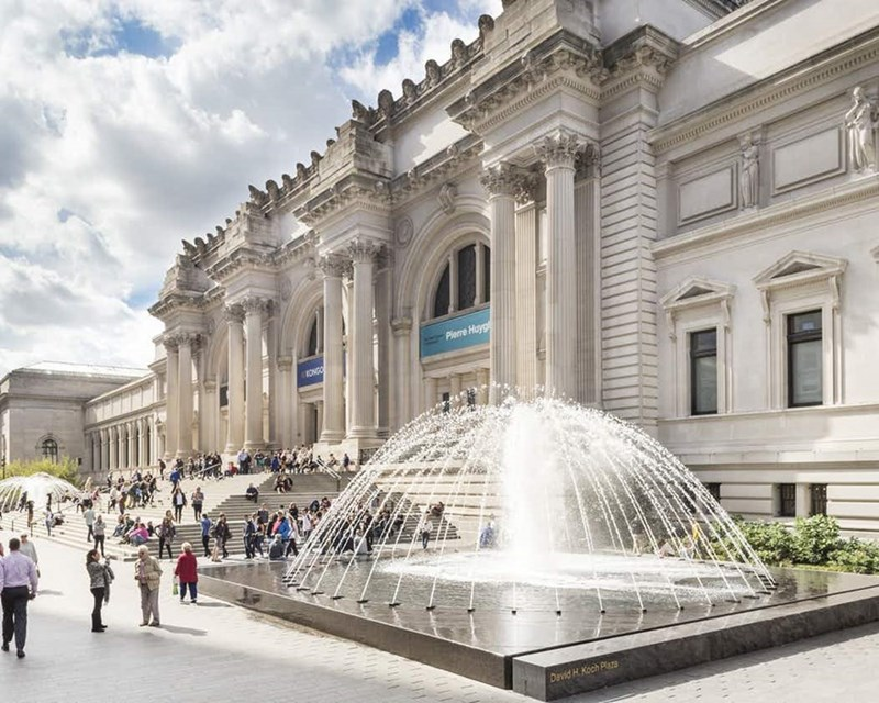 the outside of the MET museum and the fountain in front of it, with people walking in the distance