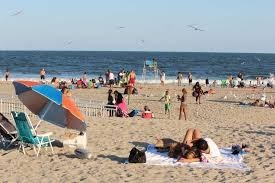 beachgoers and beach umbrellas sprinkle the sand with blue water in the background