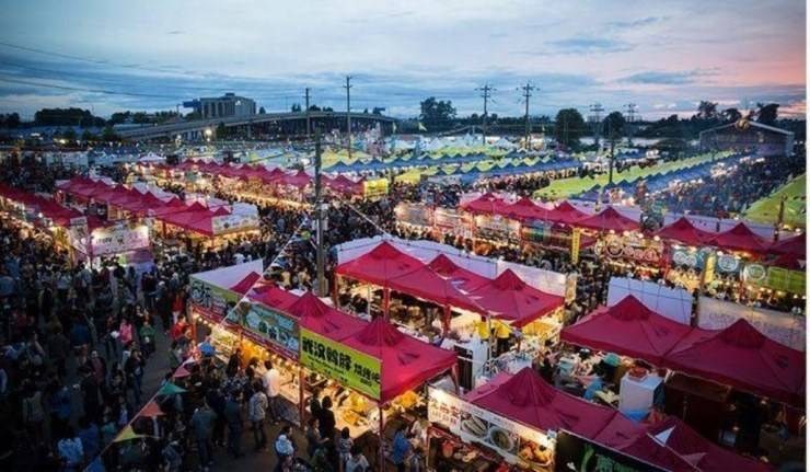 an aerial view of red tents and crowds of people at the Queens Night Market