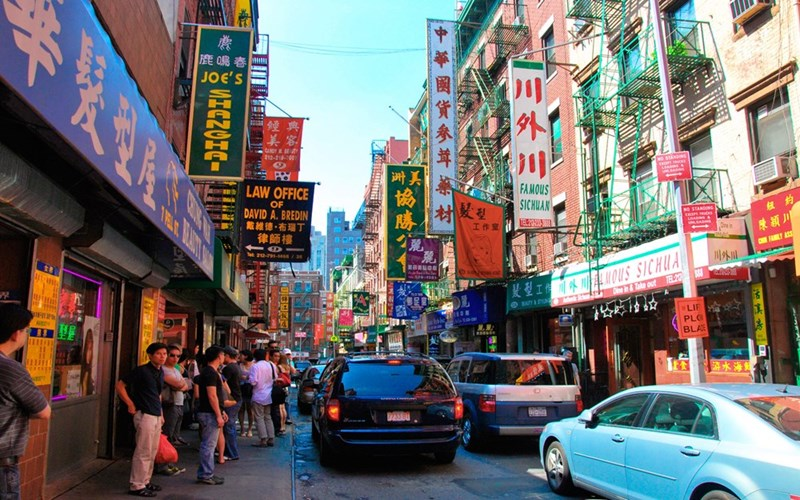 a scene of Chinatown in New York taken from street-level, showing many signs in Chinese, pedestrians walking and cars driving in the narrow street