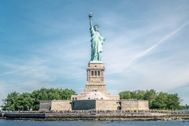 the Statue of Liberty stands in the center of the photo with the blue water below and blue sky above