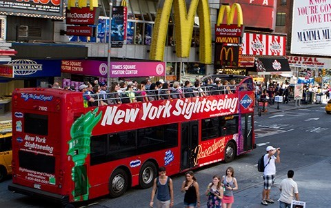 A red bus with 'New York Sightseeing' written on the side drives through the city, with pedestrians walking around it.