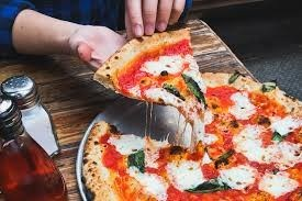 a person pulls a slice of fresh pizza from a full pizza with the cheese melting