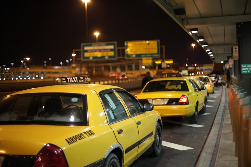 a line of yellow taxis wait outside the airport at night, with signs and lights unfocused in the background
