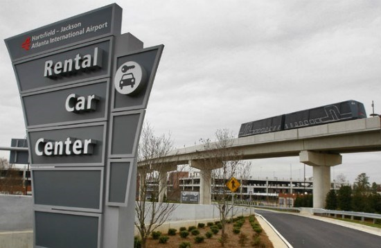 a grey sign says 'rental car center' with a road and a ramp behind it and a grey cloudy sky in the background