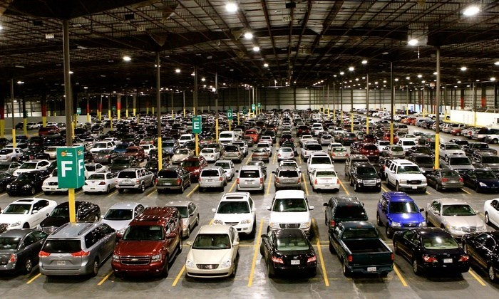 hundreds of cars sit parked inside a big industrial-looking parking lot with yellow lines marking the parking spaces