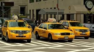 three yellow taxis wait next to each other on the road behind a white striped pedestrian crossing with beige buildings in the background