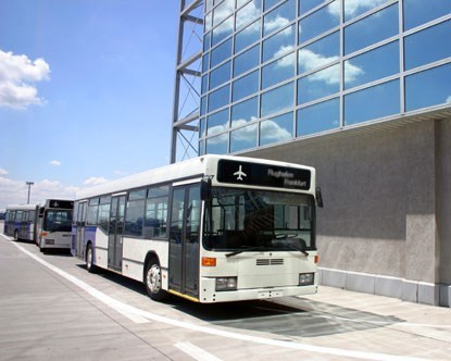 a white bus is parked in front of the corner of a sleek modern building with glass panels and the blue sky in the background