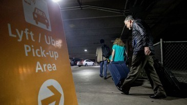 a yellow sign saying 'lyft/uber pickup area' with an arrow pointing away is on one side of the photo while passengers with rolling luggage walk along a cement ground in the direction of the arrow