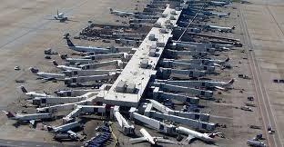 many planes are parked around one of the arms of the atlanta airport, looking chaotic and unorganized