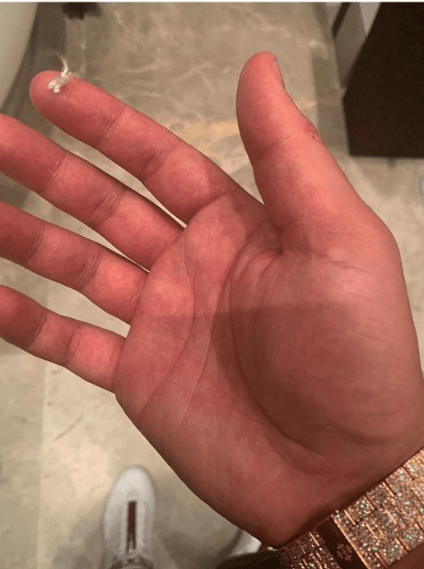 A picture of Drake holding a piece of Steph Curry's hair lint, before he offers it for sale on eBay.