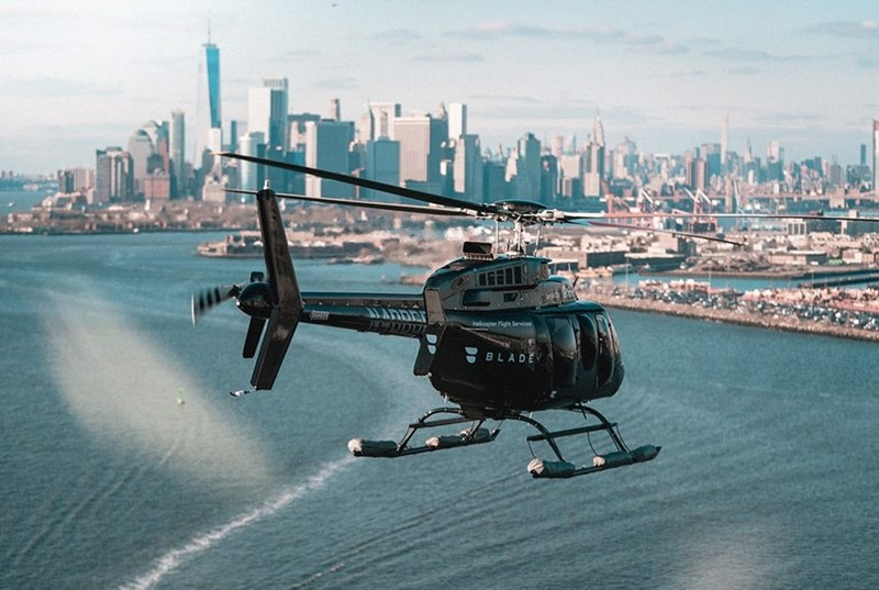 a helicopter flies towards New York City over the ocean