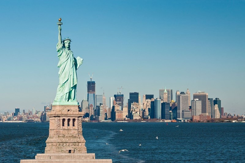 the statue of liberty stands in front of a distant New York City with water in front of the city