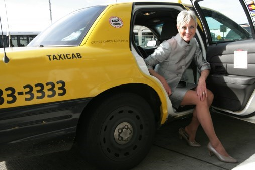 a woman sits half inside half outside of a yellow taxi