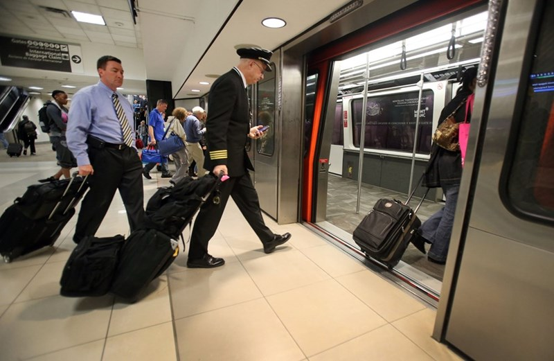 people with suitcases walk into the open doors of the skytrain in an underground station