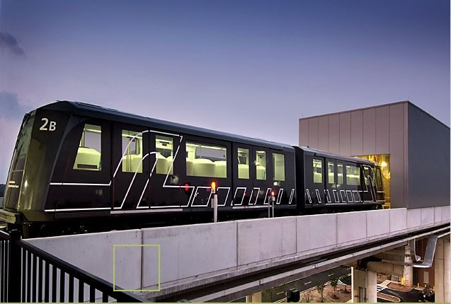 a black SkyTrain on its rails outside a square building with a purple sky in the background