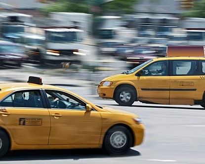 two yellow taxis drive past the camera in opposite directions with everything around them blurred