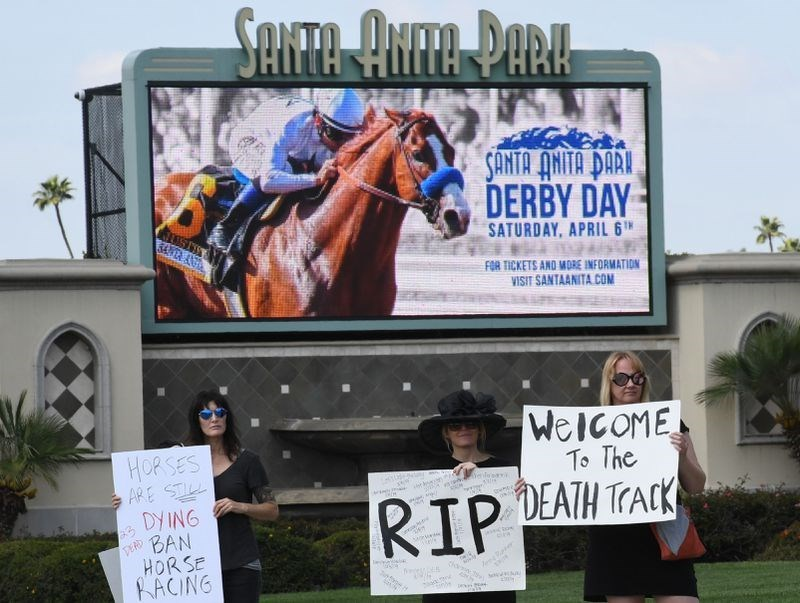 People holding RIP signs to protest the death of the horses at Santa Anita Park