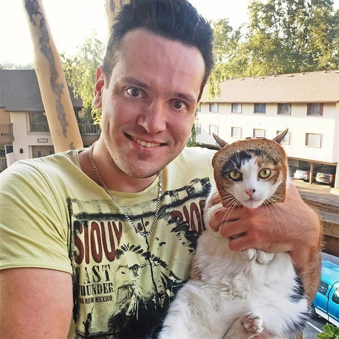 man posing with cat that has its face through a piece of bread