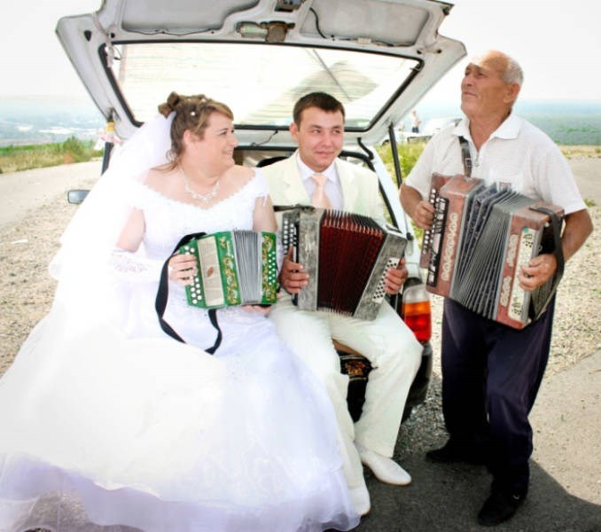 couple on their wedding day playing accordions in a car trunk
