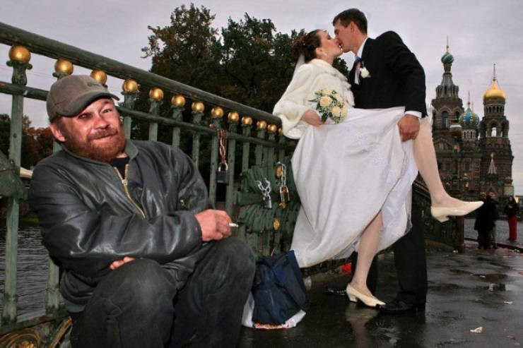 bride and groom kissing on the street behind a guy with a black eye smiling at the camera
