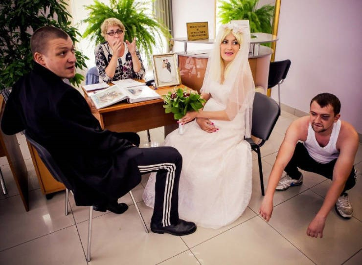 bride and groom sitting in an office with a squatting slav