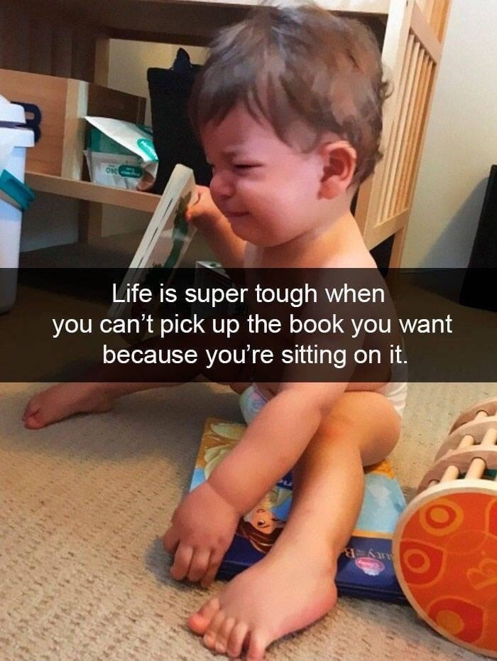 kid tantrums - Child - Life is super tough when you can't pick up the book you want because you're sitting on it.