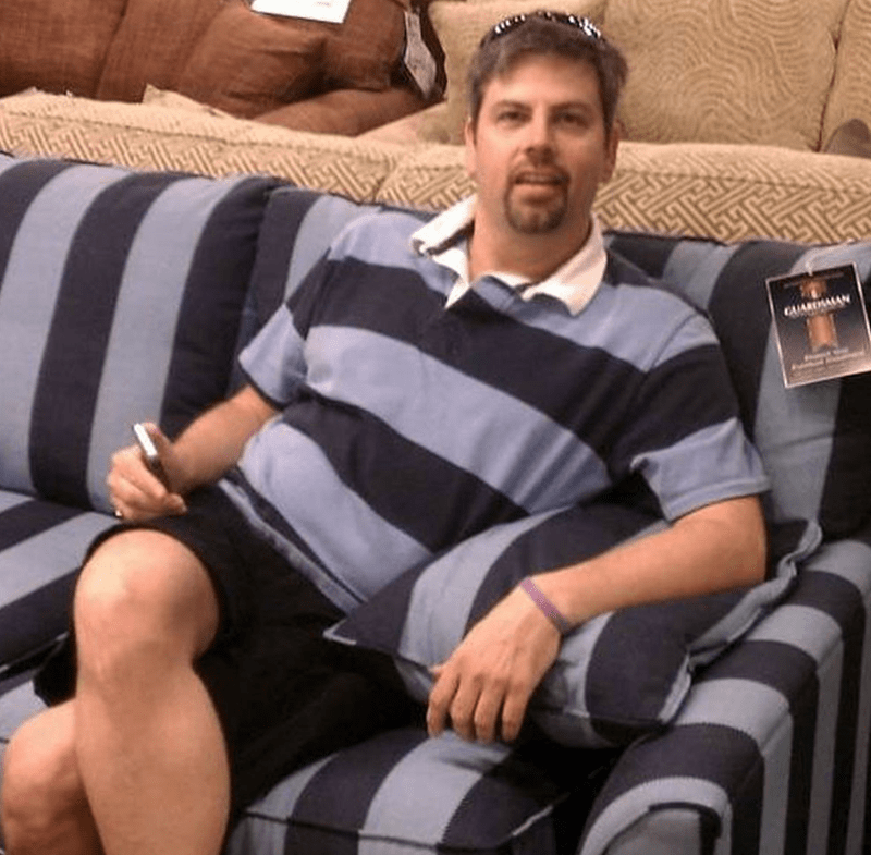 man's blue striped shirt is identical to blue striped couch