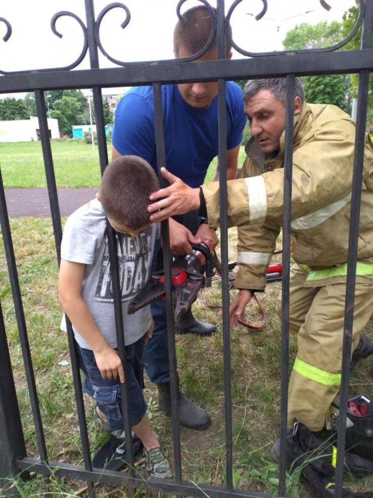unlucky kid who got his head stuck in a fence and fire man cutting it to get him out