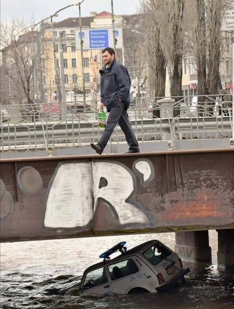 a man crosses a bridge over a sunken police car