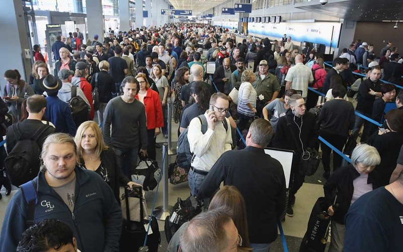 many people waiting in long lines at an airport
