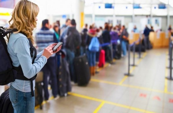 a woman in a blue shirt wearing a big backpack looks at her phone with long airport lines in the distance