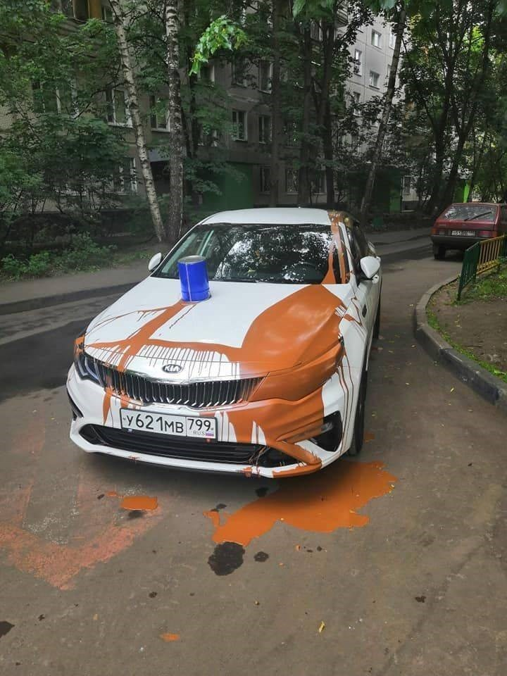 A car covered in messy orange paint.