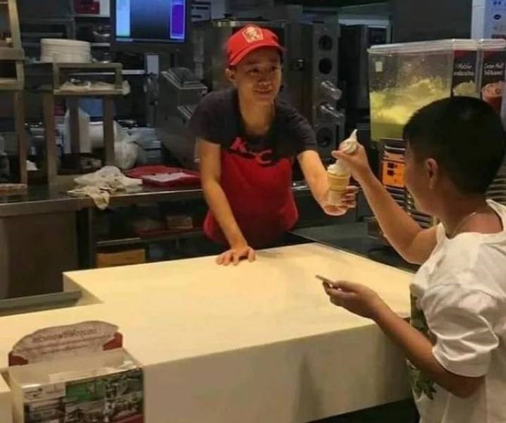 A kid grabs an ice cream cone by the ice cream.