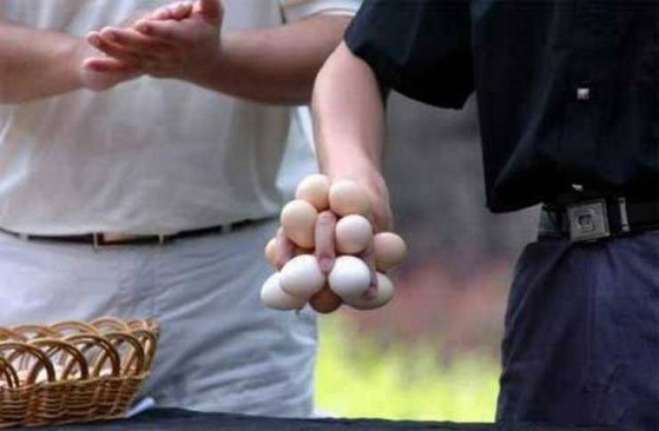 a man holds many eggs in one hand