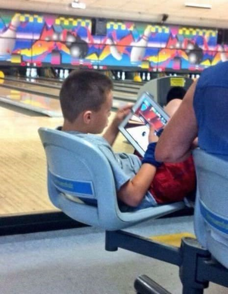Funny photo of a kid playing a bowling video game in a bowling alley