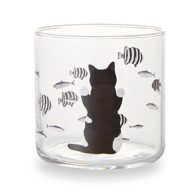 Cat looking at fish on a cup