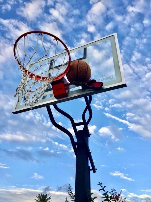 Basketball stuck between backboard and rim